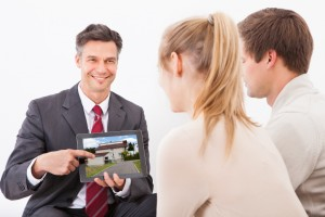 Agent With Tablet Pc Showing House To Couple