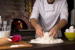 Male chef preparing dough for pizza in kitchen