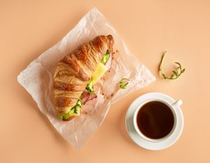 Croissant with ham and cheese and coffee cup